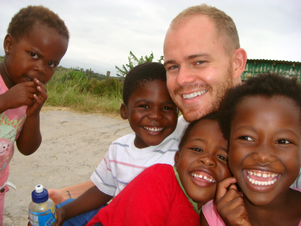 a volunteer abroad with children from a village where he is volunteering and living.