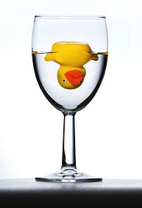 Photo of a duck upside down in a wine glass.