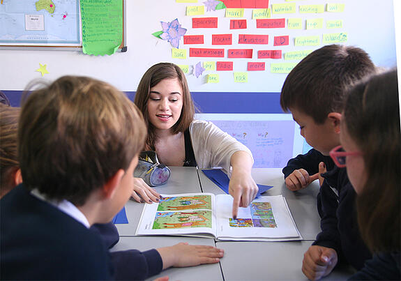 A GeoVisions paid teacher holding an ESL class in Spain with 3 younger students.