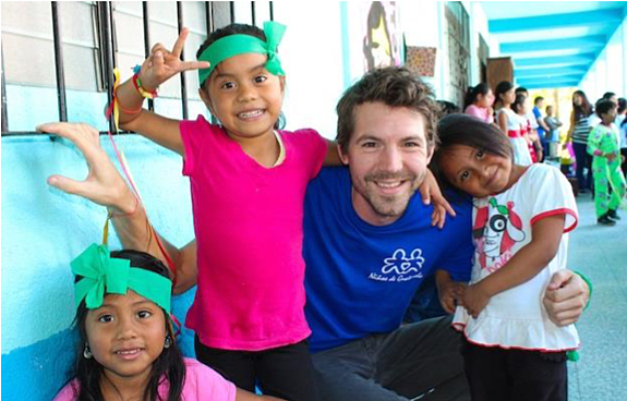 A GeoVisions volunteer in a school in Guatemala with 3 of his students.