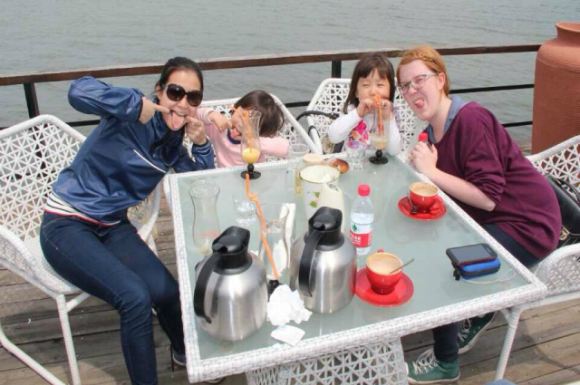 Two GeoVisions au pairs in China with their host sisters having lunch.