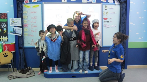 A GeoVisions teacher in China with her six students rehearsing a play in English.
