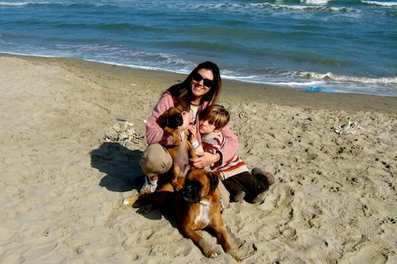 An au pair on the beach in Italy with her host brother and their dog.