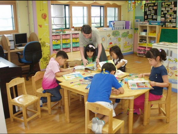 Five South Korean English students around a table with their GeoVisions English teacher.