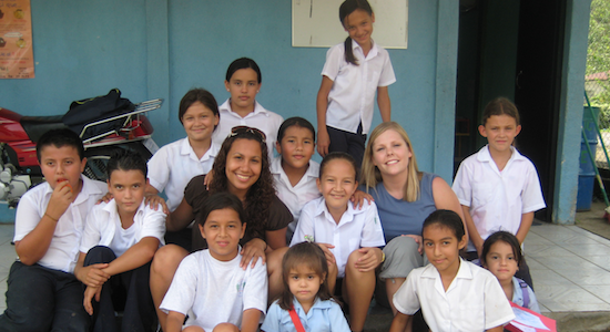 Two GeoVisions teachers with their Costa Rican students sitting outside in front of their local school.