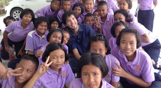 A GeoVisions paid English teacher with his students in Thailand posing for a group photo.