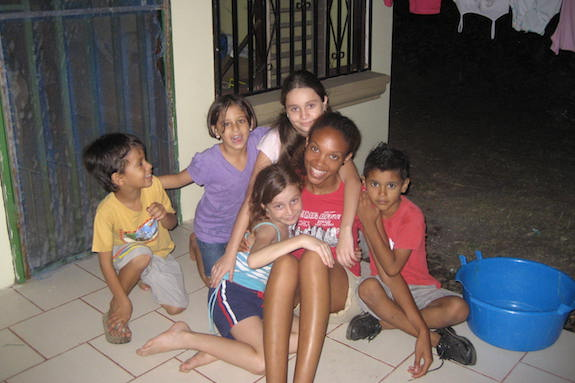 A GeoVisions volunteer teacher with some of her students outside the school.