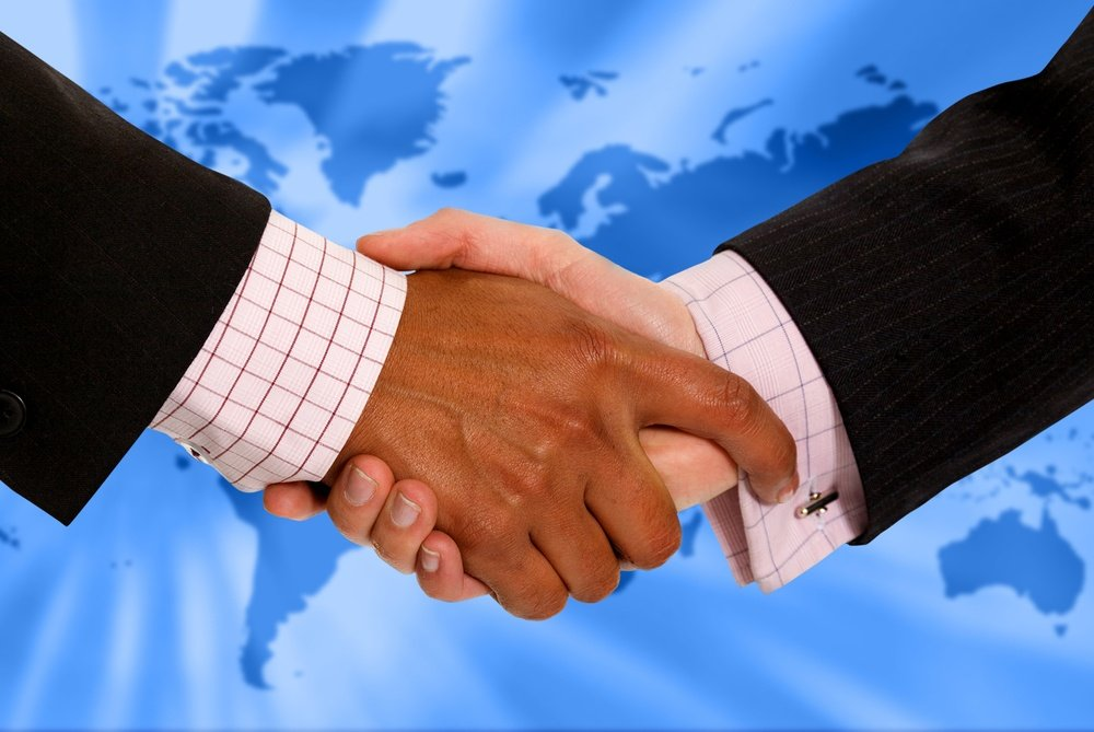 Business people handshaking with a world map at the background