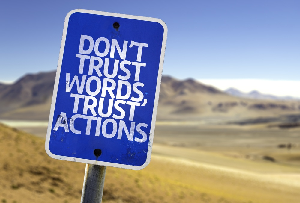 Don't Trust Words, Trust Actions sign with a desert background
