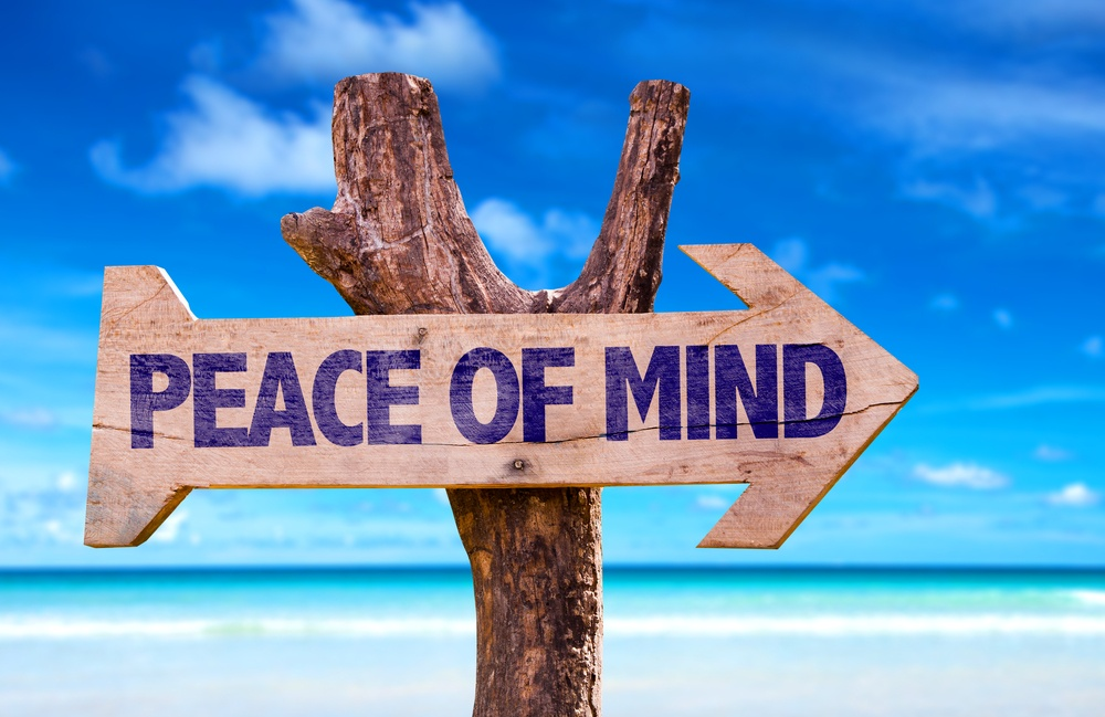 Peace of Mind wooden sign with beach background