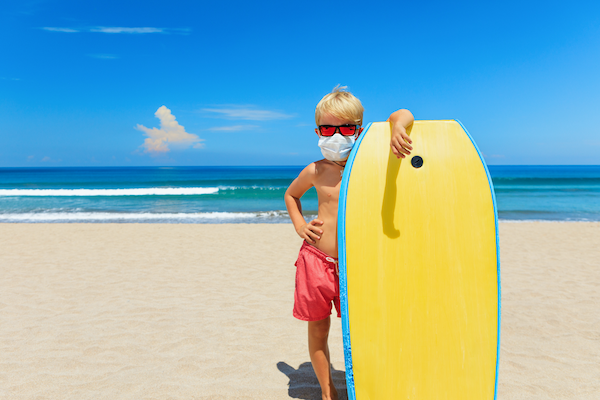 surfer boy on the beach with a covid-19 mask