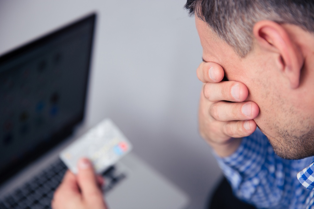 Upset man holding credit card with laptop on background