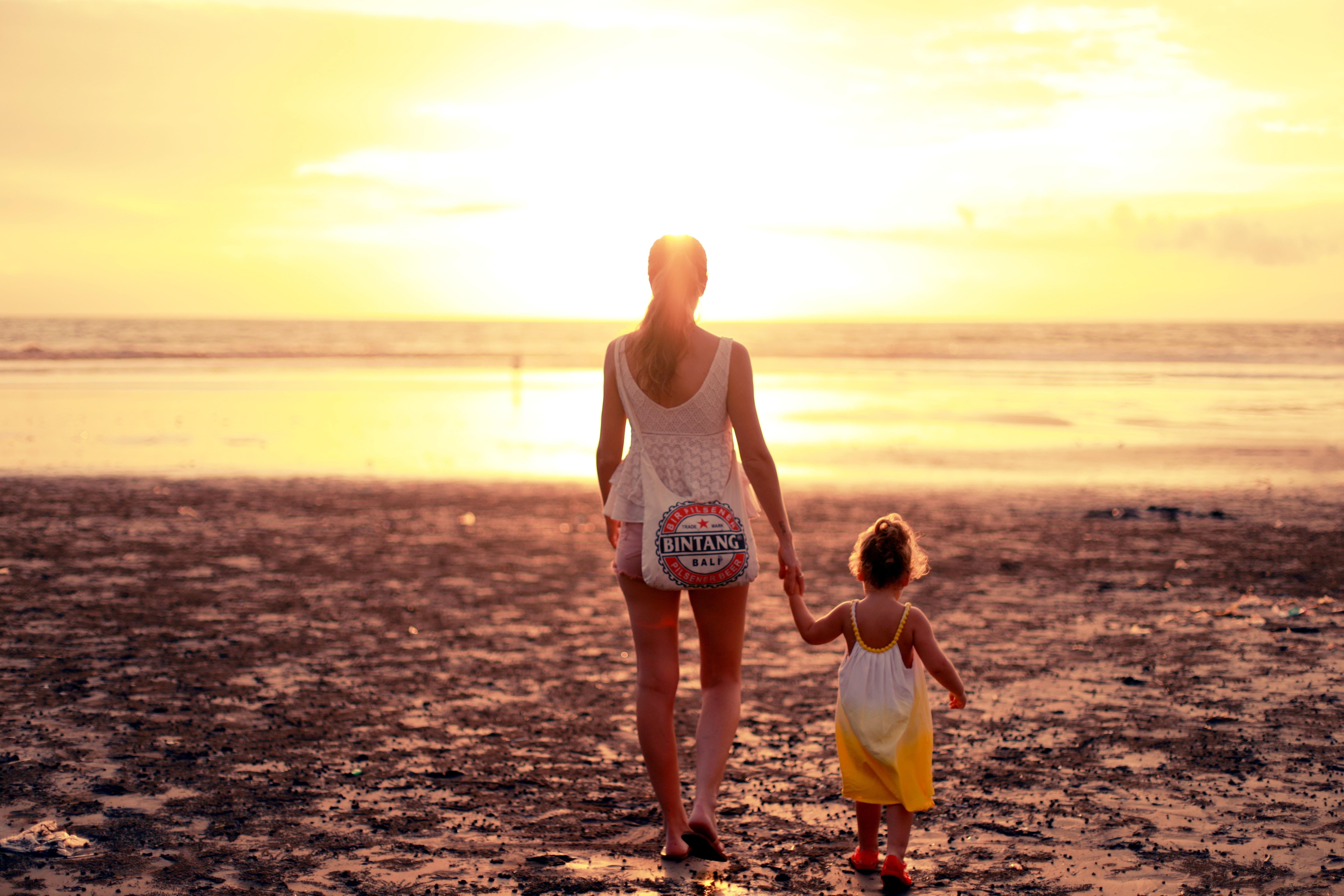 an au pair walking on the beach toward the ocean with her host sister