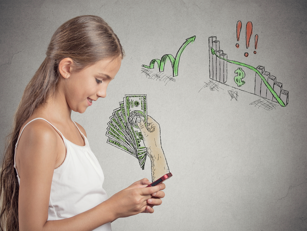 business on a go. Teenager girl working online on smart phone making earning money, hand with dollar bills banknotes reward coming out of phone screen isolated grey background. Human face expression